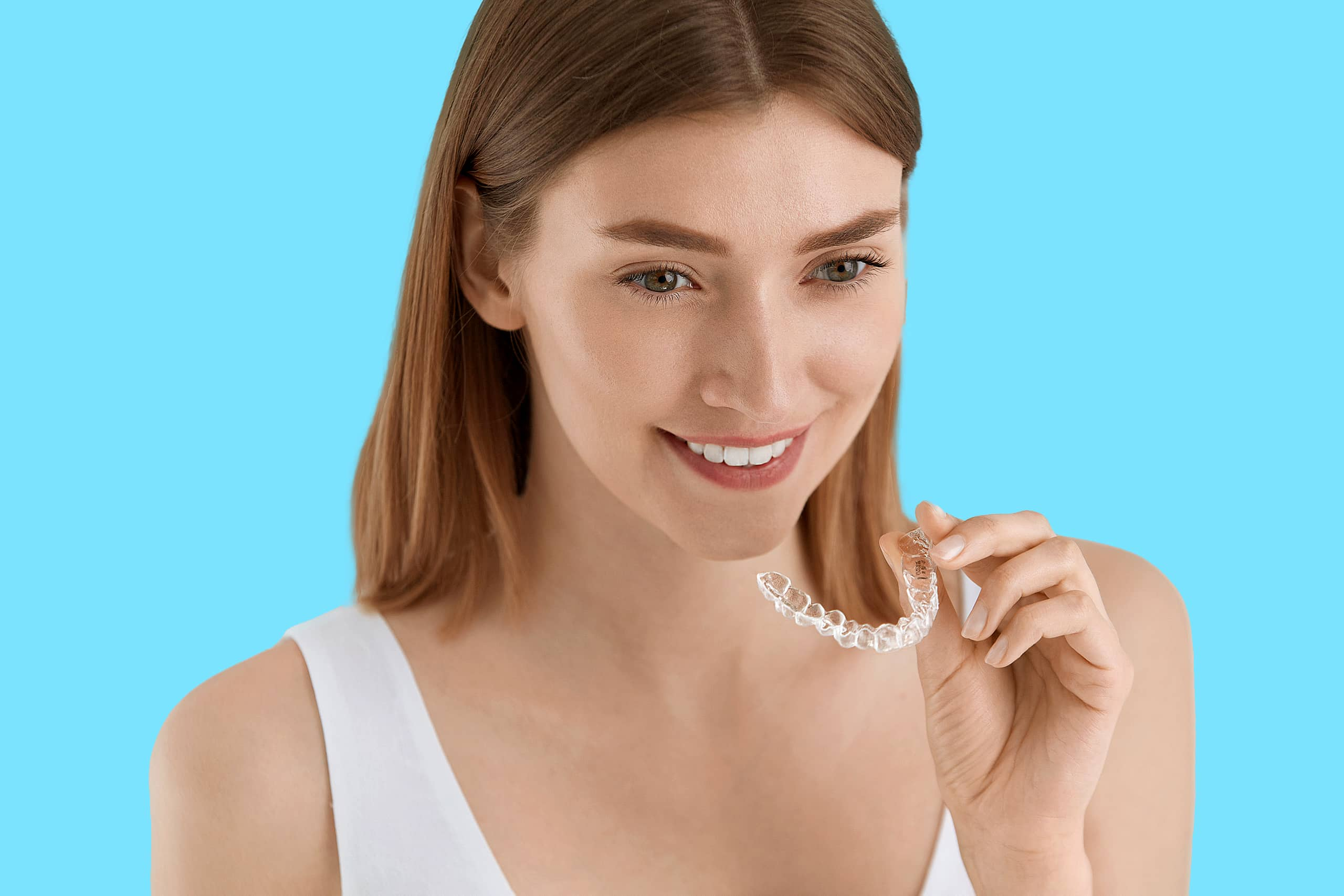 Woman with clear aligner in her hand